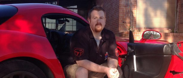 Man sitting in Red Dodge Viper