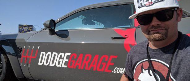 man taking a selfie with Dodge Garage promo challenger