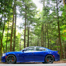 Blue 2018 Dodge Charger SRT Hellcat parked alongside road with towering trees in the back ground