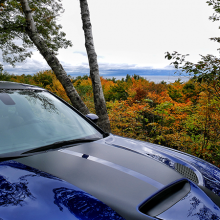 Blue 2018 Dodge Charger SRT Hellcat driving along road with trees changing color
