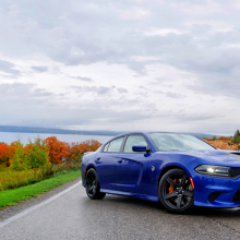 Blue 2018 Dodge Charger SRT Hellcat parked on street with trees changing color in the background
