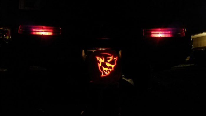 Dodge Demon pumpkin in front of the back end of a Dodge Demon