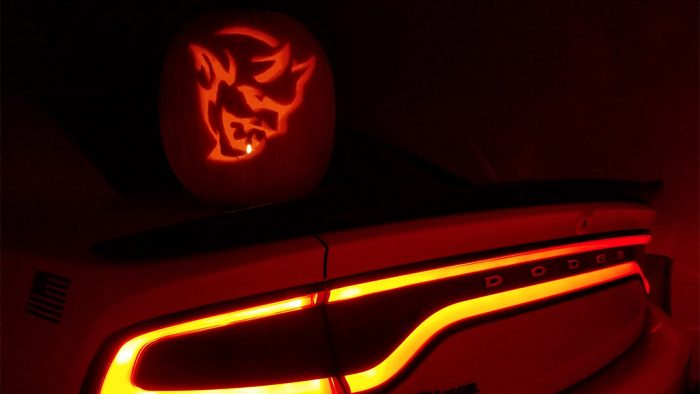 Dodge Demon pumpkin sitting on the trunk of a Dodge Charger