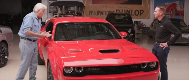 Jay Leno talking to Steve Beahm around a red Dodge Challenger
