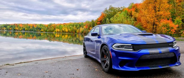 Blue 2018 Dodge Charger SRT Hellcat parked along a lake with color changing trees in background