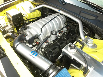 Adorned with a Mopar Performance cold air kit and strut tower brace, the original 6.1-liter HEMI® was bored and stroked to a full 426 cubes. The fabricated Moroso coolant reservoir adds drag strip pit vibes.