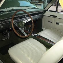 The standard GTS interior was far more inviting than the sparse void of typical Dodge Package Cars. This one has the optional wood-grain sport steering wheel, a $26.75 upcharge. Unlike the 150 mph speedometer used in 440 Magnum-powered Chargers and Coronets, the standard 120 mph Dart speedometer was retained aboard every 440 GTS. The optional ($50.15) console-mounted 6,000 rpm tachometer looks great but is too low for easy use.