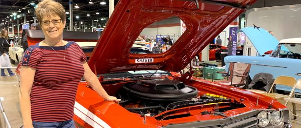 Lena Plymale standing beside her 1971 Dodge Challenger Convertible at MCACN