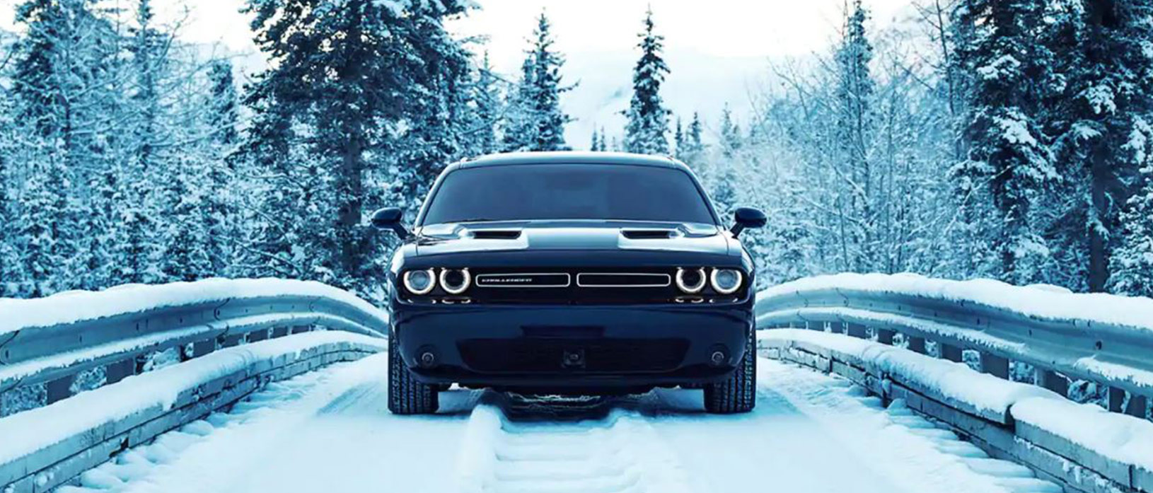 Dodge Challenger driving across a bridge in the snow