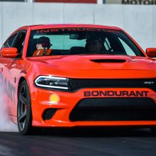 Drag Strip Showdown Winner doing a burnout in an orange Charger Hellcat