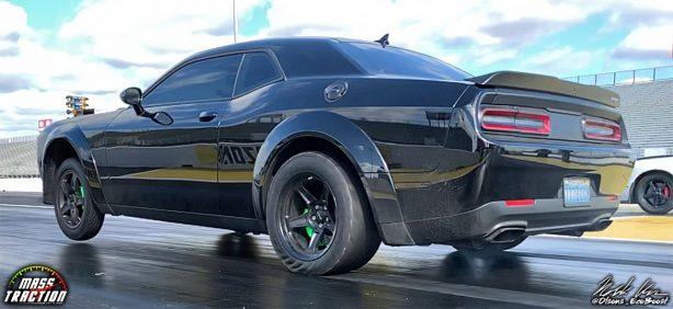 Black Dodge Demon racing down the track