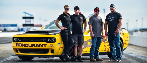 Drag Strip Showdown winners posing with Matt Hagan & Leah Pritchett in front of a yellow Bondurant Challenger