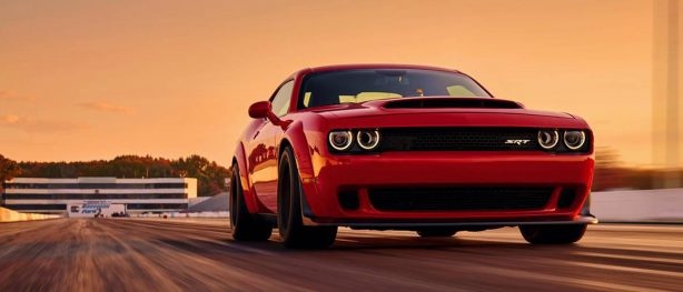 Red Dodge Challenger SRT Demon racing down the track