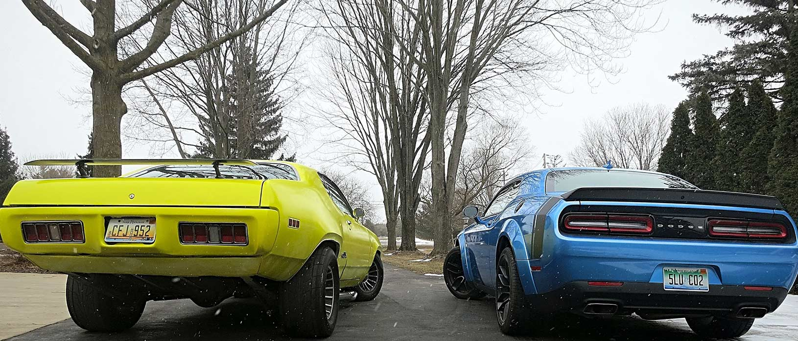 Rear end of yellow GTX and blue Challenger