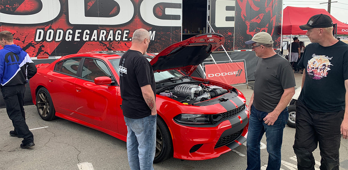 Attendees of Spring Fest looking at the engine of a red Charger