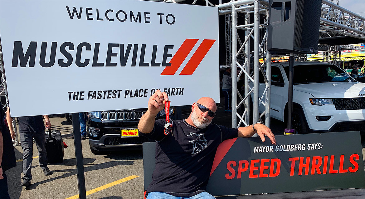 """Bill Goldberg holding up his red key sitting on a bench that says """"Mayor Goldberg Says: Speed Thrills"""" with a sign in the background that says """"Welcome to Muscleville The Fastest Place on Earth"""""""