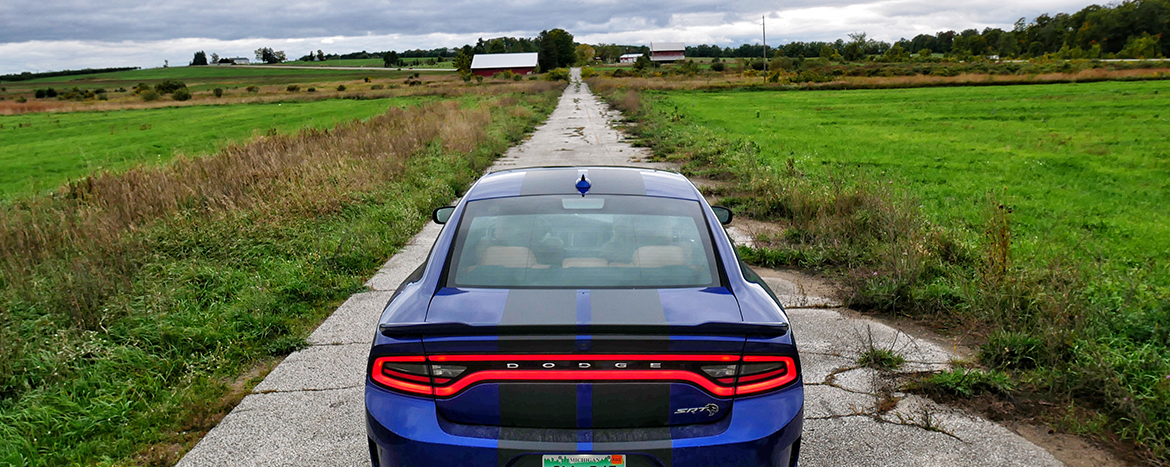 Blue Charger Hellcat driving down a deserted road