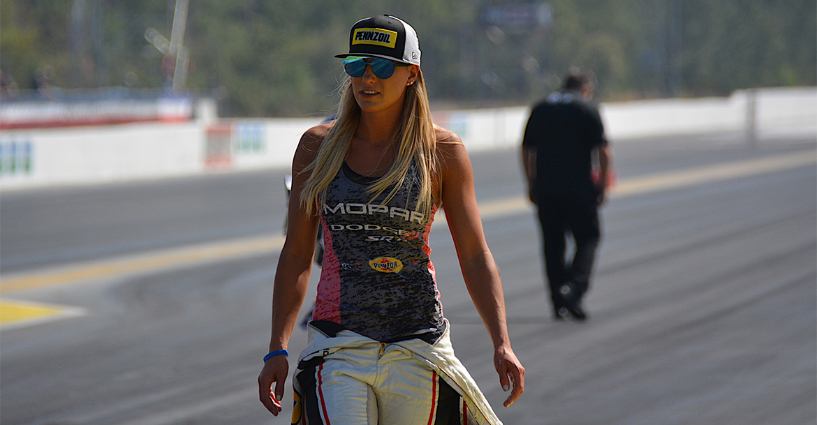 Leah walking down the track wearing a Pennzoil hat and race suit