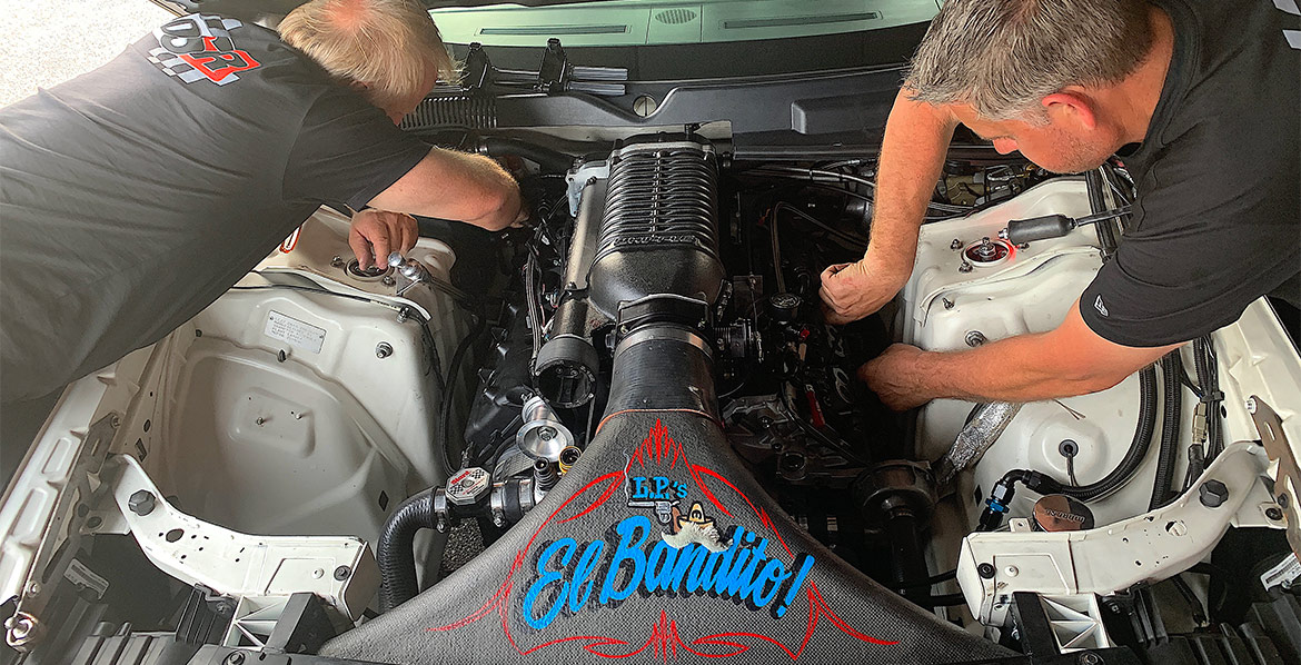 Leah's crew working on the engine of her Challenger Drag Pak