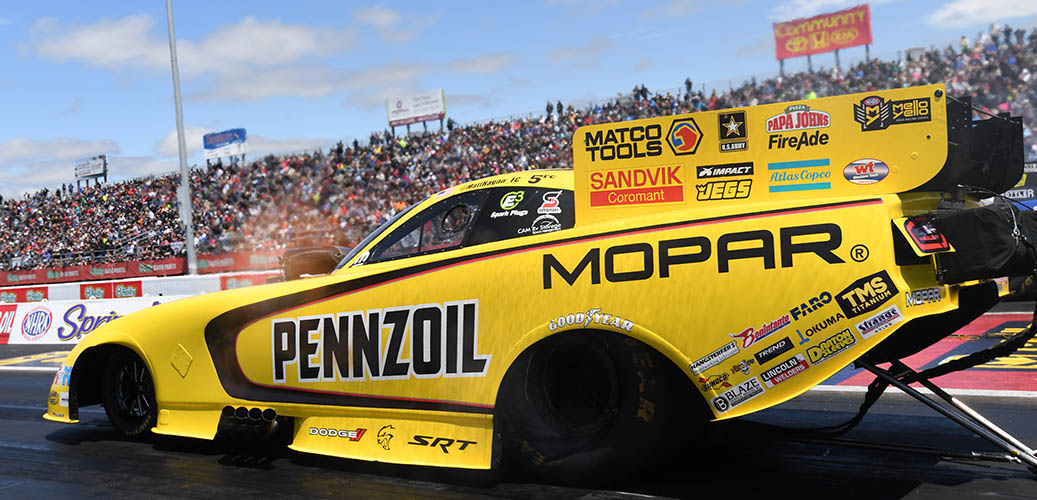 Matt Hagan preparing to race his Dodge Charger SRT Hellcat Funny car down the track with stands full of fans looking on