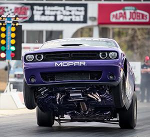Purple Challenger doing a wheelie off the start line