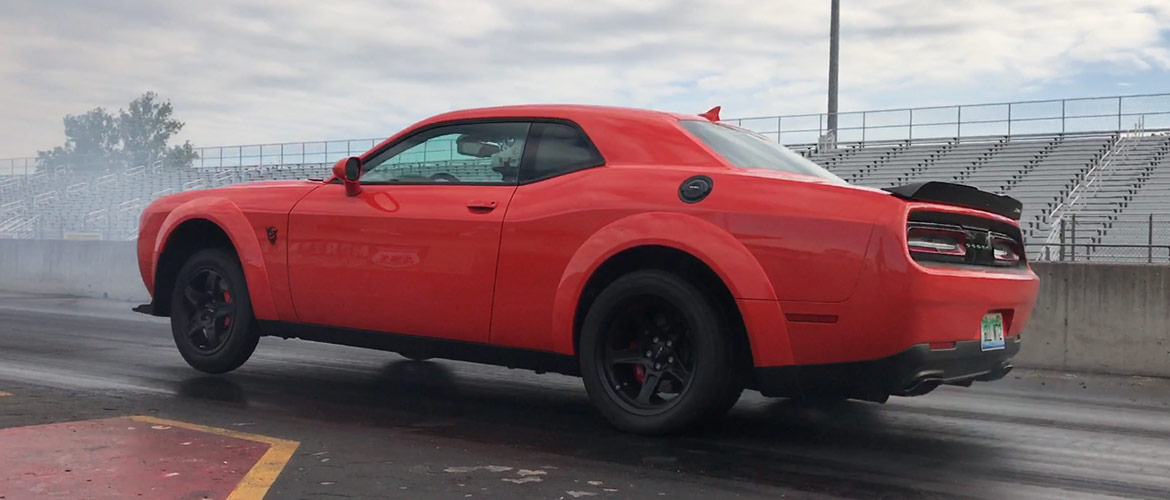 Red Dodge Demon pulling a wheelie off the start line