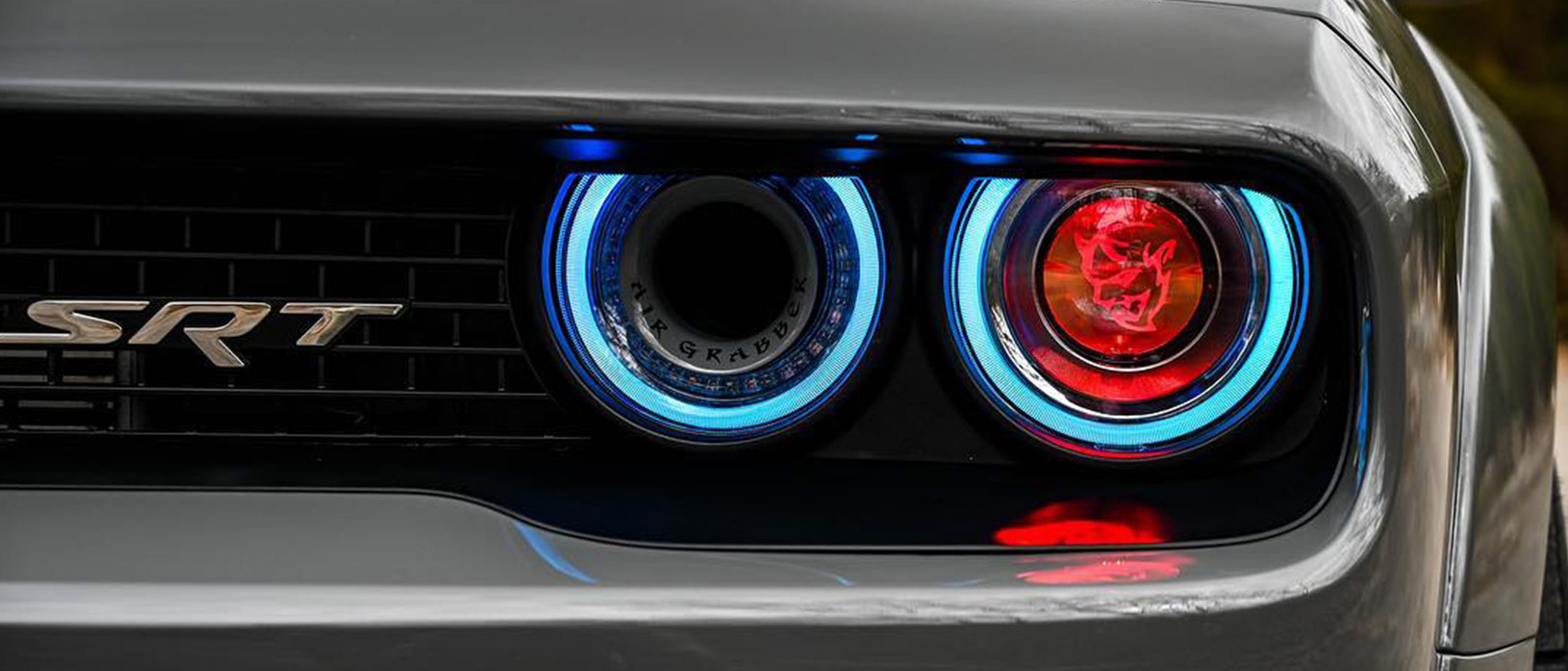 Headlights of a Dodge Demon with a Demon head in the center