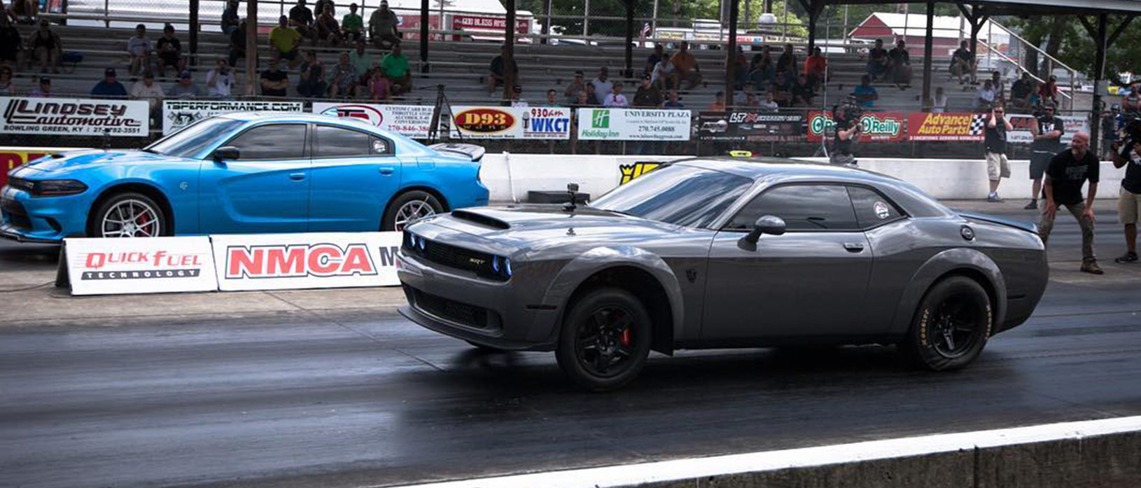 Gray Dodge Demon racing a blue Charger Hellcat
