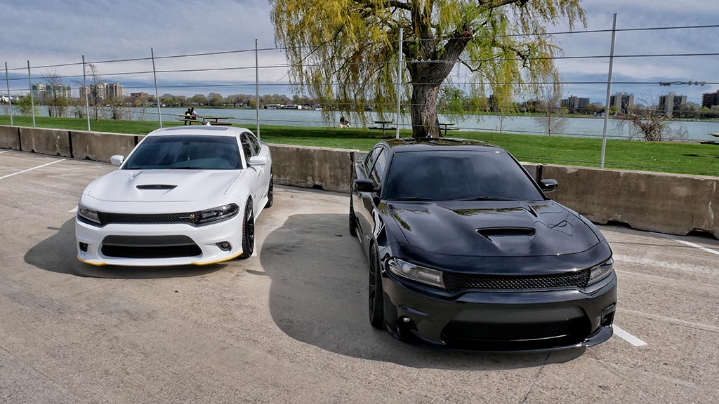 Two black and white dodge chargers side by side