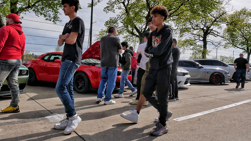 teens walking by dodge vehicles lined up