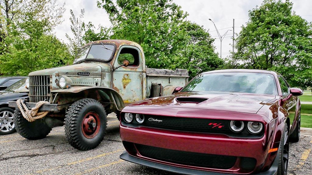 Red Challenger R/T next to vintage Dodge truck