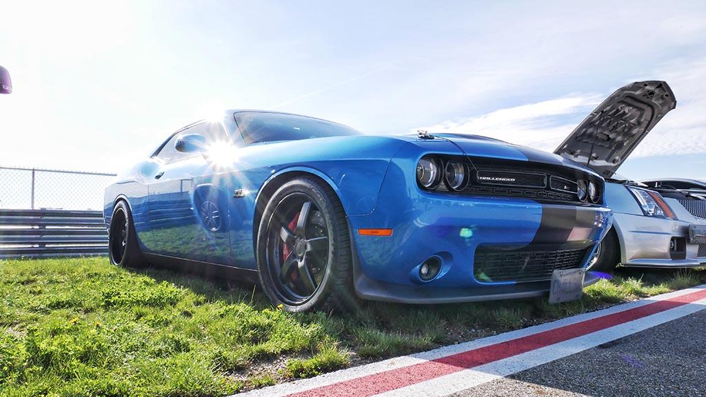 Side view of blue Dodge Challenger SRT with matte black racing stripe