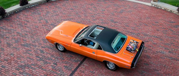 Orange 1970 Dodge Challenger with black top and sunroof