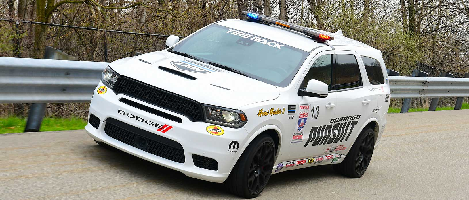 White Dodge Durango SRT Pursuit with race decals driving around a track