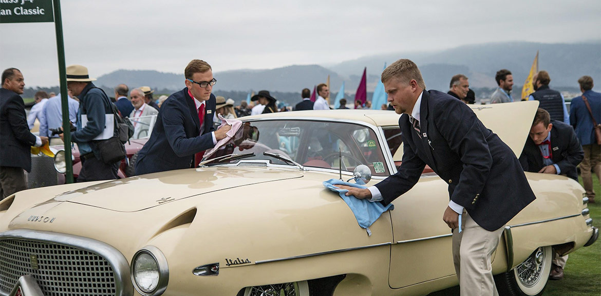 McPherson College students prepare a 1953 Hudson Italia Prototype Touring Coupe before they drive it onto the field at Pebble Beach.