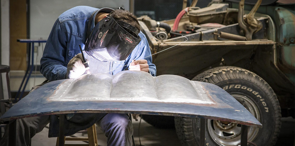 A student works in the sheet metal lab on a custom built hood