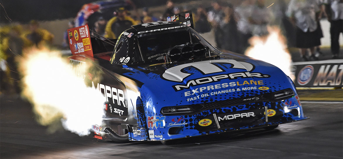 Mopar Express Lane Dodge Charger Hellcat Funny Car racing down the track with flames shooting out of the sides