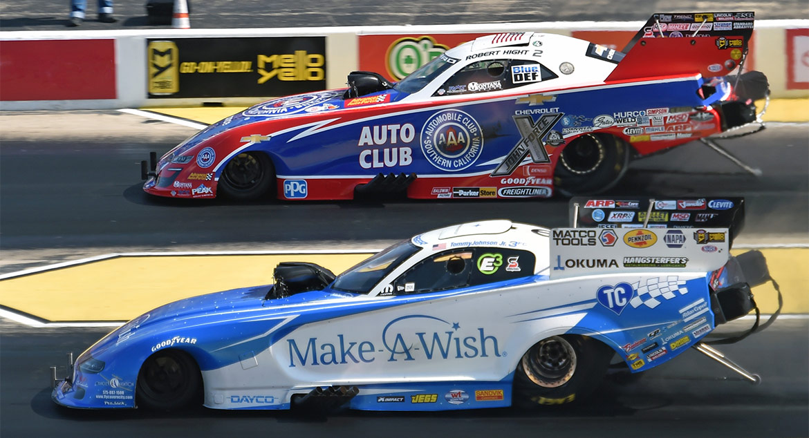 Two funny cars racing down the track at NHRA Route 66