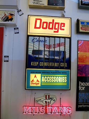 "Dodge air conditioning sign that says ""Choose your climate, keep comfortably cool"". Neon mustang sign below."