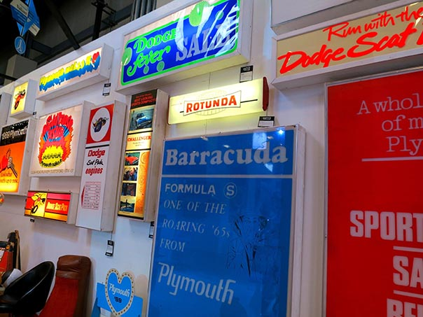 Array of backlit Dodge, Rotunda, and Barracuda signs.