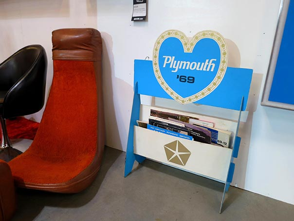 Plymouth '69 magazine holder next to a red chair.