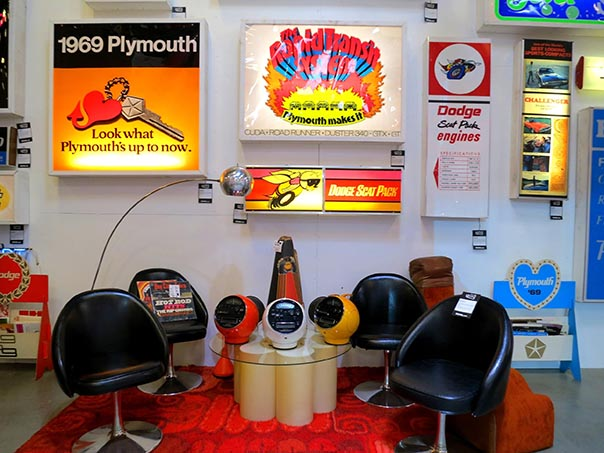 70's sitting area against wall of backlit signs.