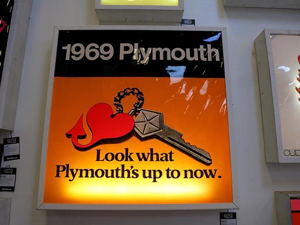 "Backlit sign of a Plymouth keychain reading, "" 1969 Plymouth. Look what Plymouth's up to now."""