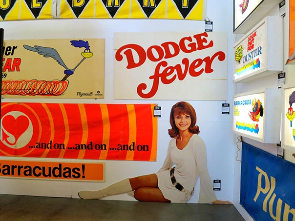 Different car related posters from the 70's. Woman in a gogo outfit sitting below a dodge fever sign.