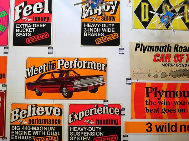 "Different car related posters from the 70's. Front and center is a challenger poster that say ""Meet the Preformer""."
