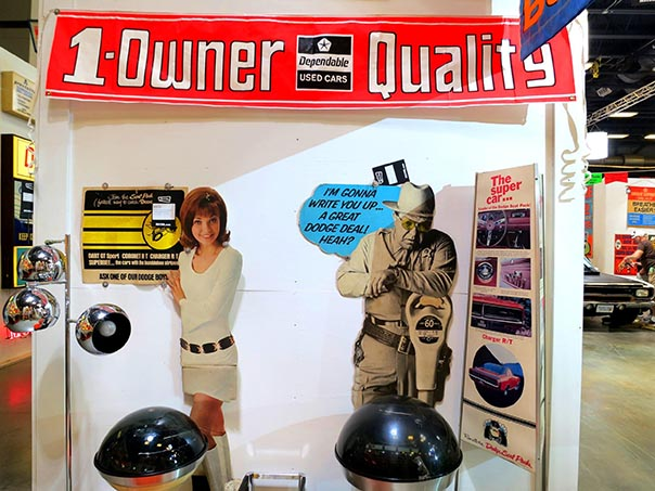 "White wall with a banner at the top reading ""1-Owner Quality"". Below on the left a young girl with a all white outfit on hols a sign. On the Right a cutout of a police officer saying,""I'm gonna write you up... a great dodge deal! heah?"