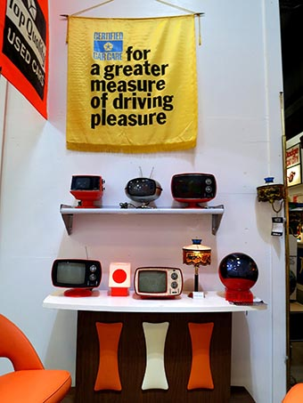 "70's style decor, at the top of the white wall a banner reads ""for a greater measure of driving pleasure"". Below sits a shelf and cabinet with different raidios and lamps"