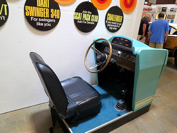 Model of the drivers seat and steering wheel of a old car that is pale blue