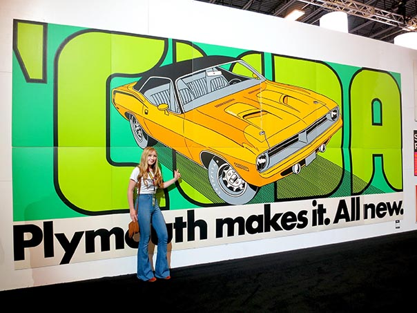 Young lady posing infront of a wall size yellow 'Cuda poster that reads, 'Plymouth makes it. All new.'