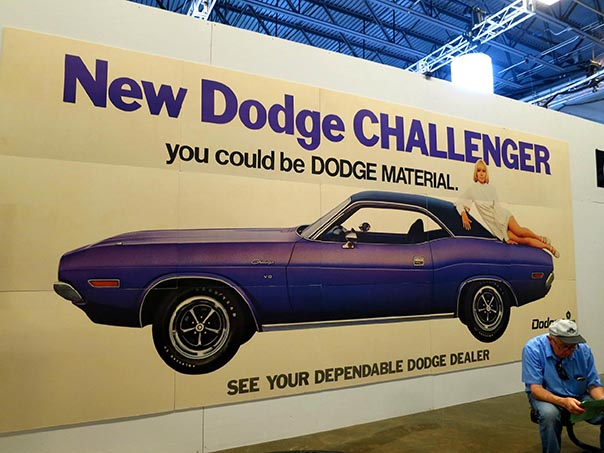 Large poster of reading,'New dodge challengers you could be dodge material' with a purple challenger convertible.